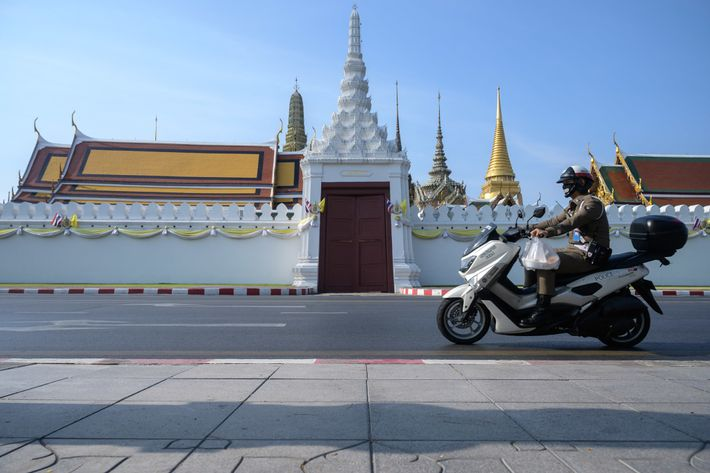 A masked police officer clutches a bag of takeout food as he rides past the Gate ...