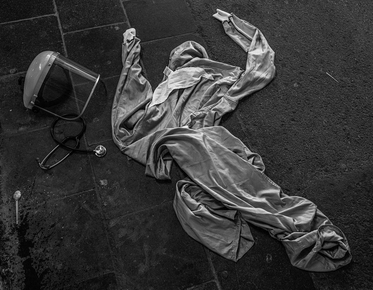 A doctor's personal protective equipment (PPE) is strewn on the ground outside a hospital in La ...