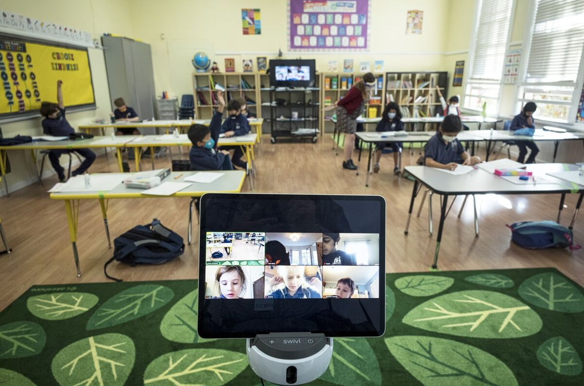 A monitor displays students learning remotely while others attend class in-person at a San Fransisco elementary ...