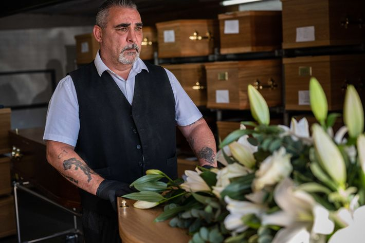 Sean Kill, the foreman at Stoneman Funeral Service, makes final preparations on the coffin of a ...