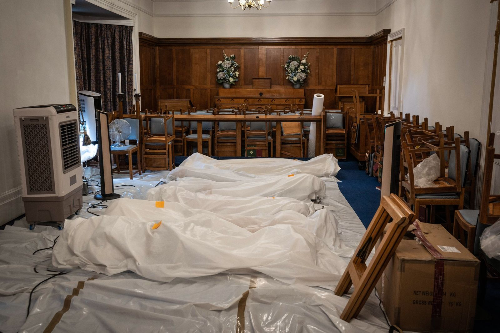 An overflow of bodies is laid out on the floor in the chapel of a funeral ...