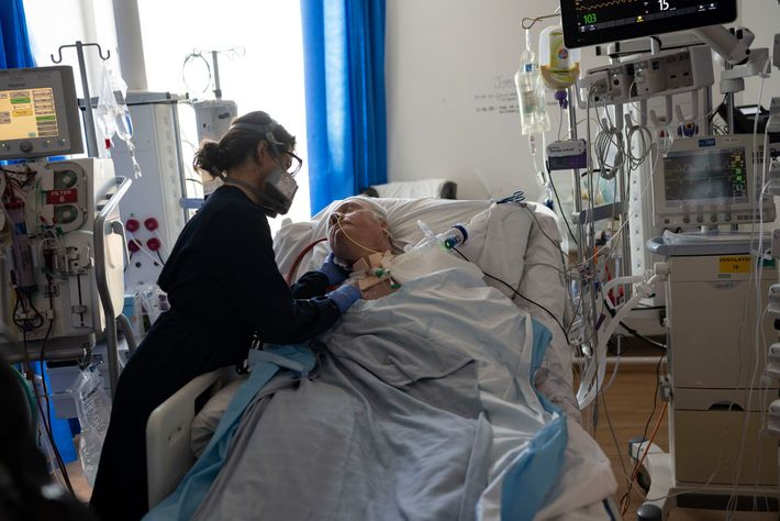 Nurse Josephine Riccobono comforts COVID-19 patient William Ferguson who has been hooked up to an ECMO ...