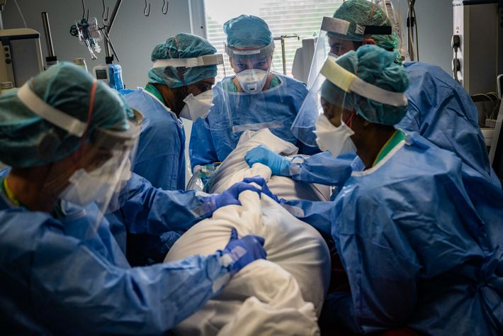 Anaesthesiologist Caroline Borkett-Jones leads a team turning a suspected COVID-19 patient from their back onto their ...
