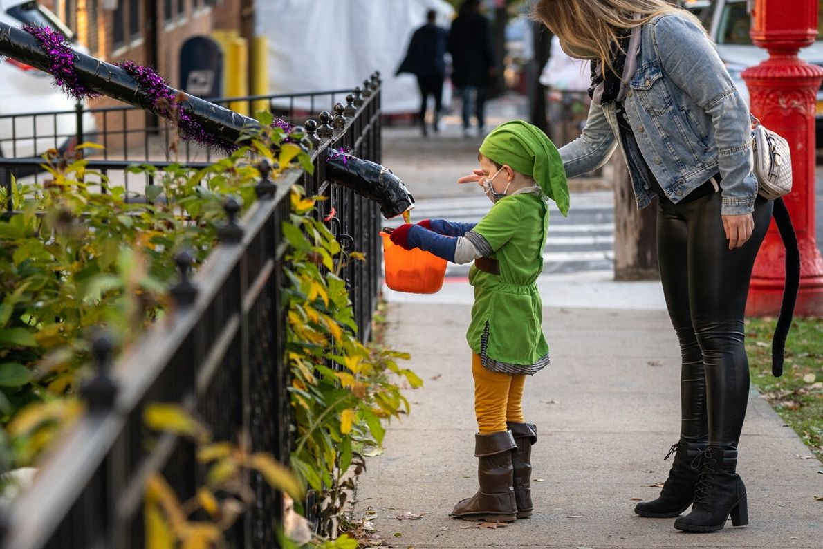 A chilid receives Halloween treats via a candy chute in New York Ciity.