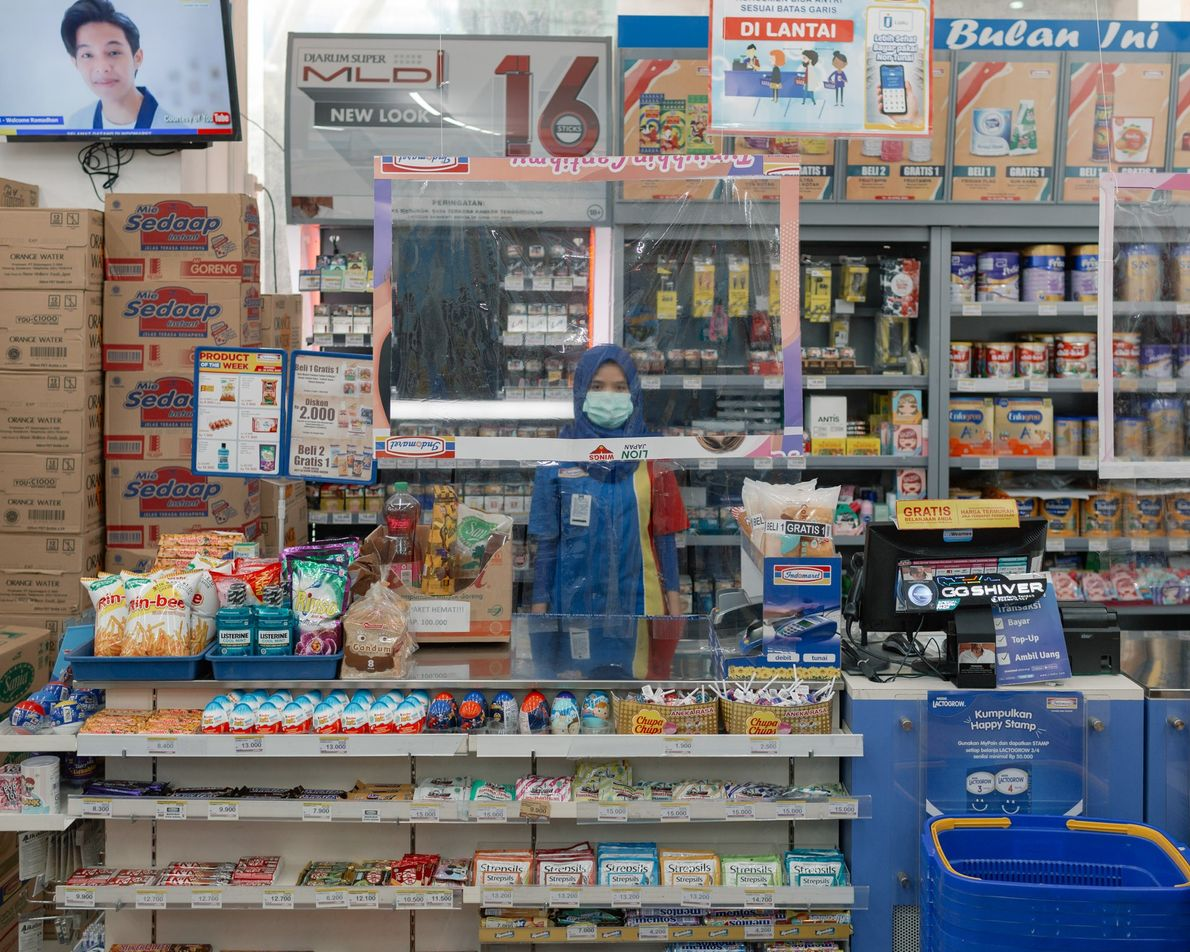 A convenience store clerk in Bandung wears a mask and stands behind a plastic screen to ...
