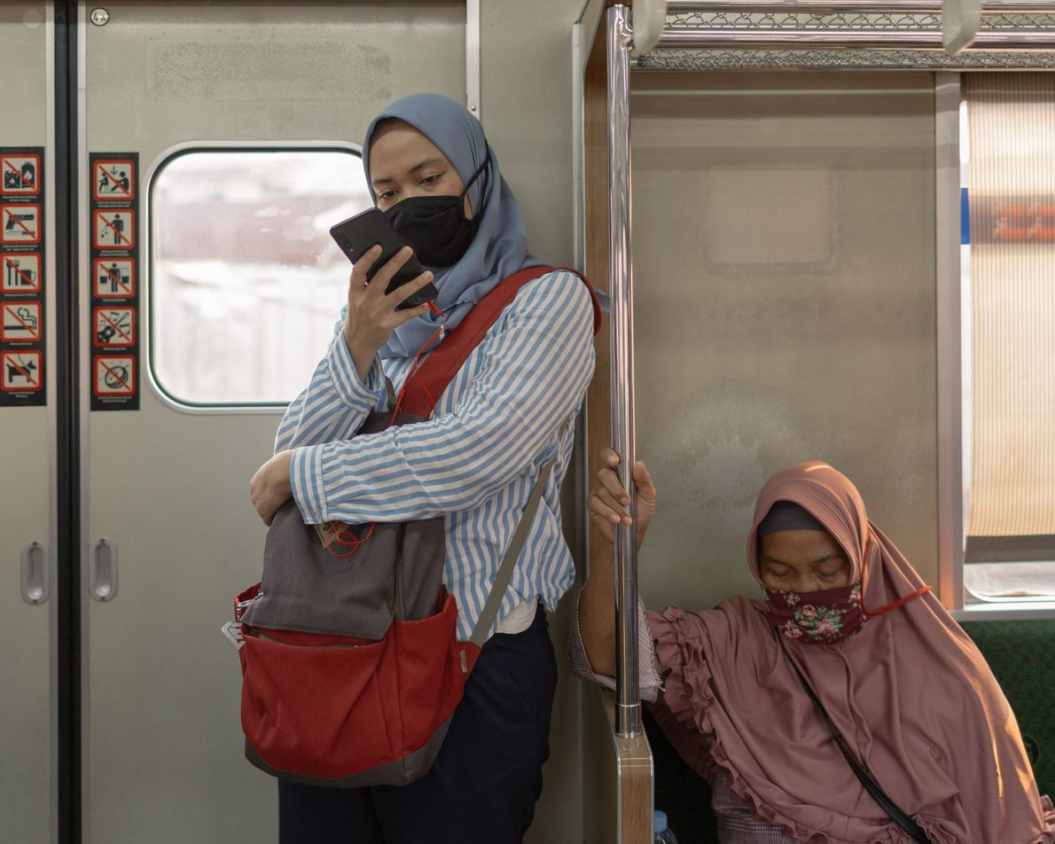 Two women ride the suburban commuter train in Jakarta, the epicenter of the pandemic in Indonesia ...