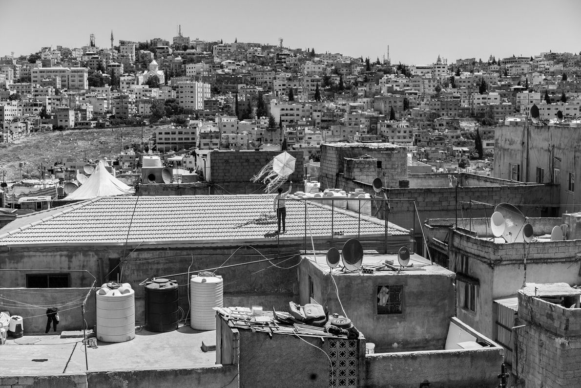 During lockdown in Amman, a young Jordanian flies a kite on a rooftop. Businesses in the ...