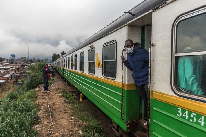 Commuters wearing face masks stand in the morning train that stops at Kibera every day en ...