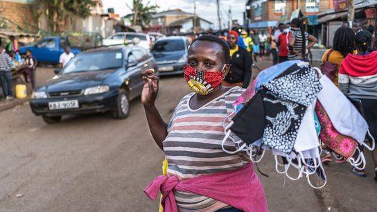 A woman sells homemade face masks along a busy street in Kibera after the government mandated ...