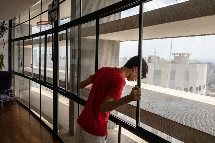 David Sabino, 14, peers out from his family's sprawling apartment on the 31st floor of the ...