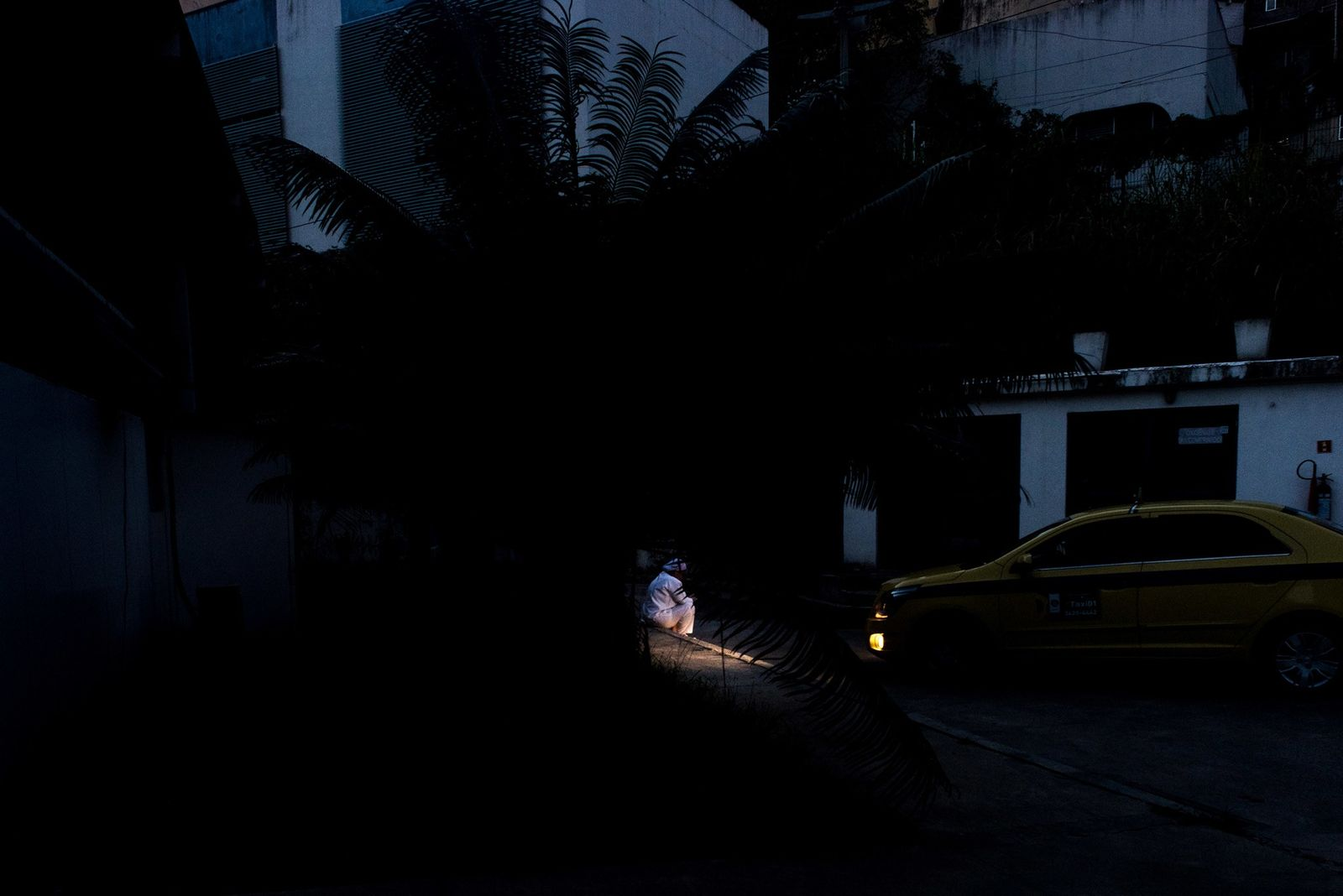A healthcare worker taking a break is illuminated by the headlights of a taxi bringing a ...