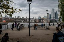 Pedestrians walk along the Riv​er Thames in London, October 18, ​2020. Tough restrictions on movement have ...