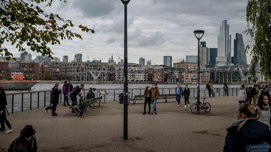 Pedestrians walk along the River Thames in London, October 18, 2020. Tough restrictions on movement have ...