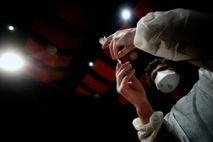 A nurse prepares a syringe with the Moderna COVID-19 vaccine, based on mRNA technology, at a ...