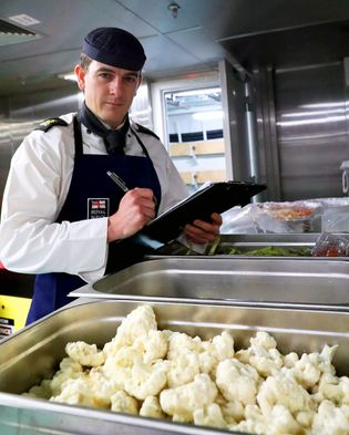 Food is prepared in the ships galley, HMS Queen Elizabeth. The entire crew can be served ...