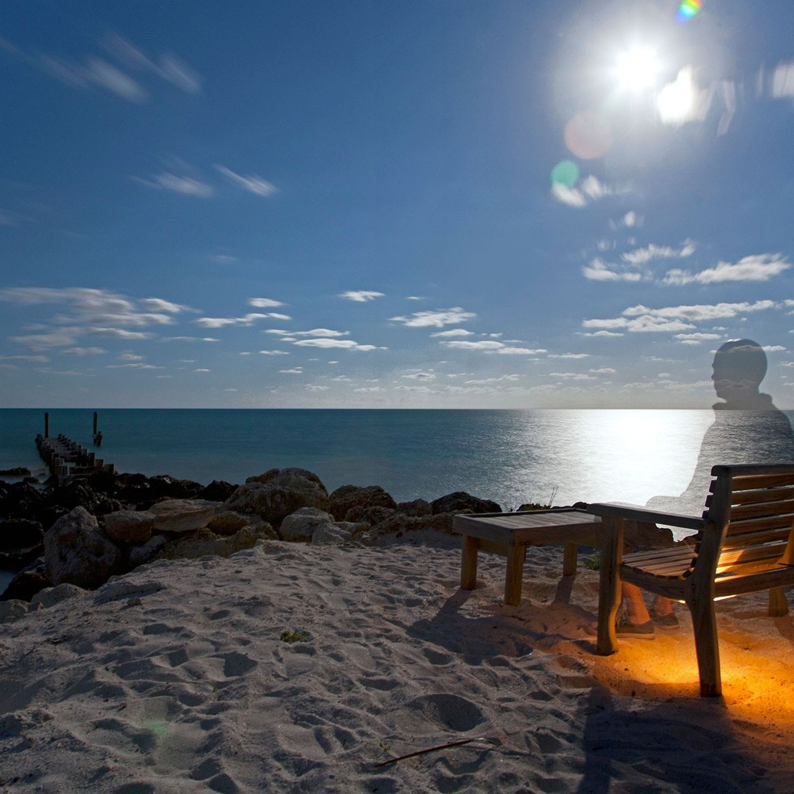 A long-exposure photograph shows a ghost-like image of a man sitting at a beach in the ...