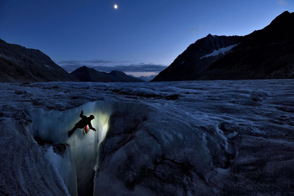 A cave explorer begins an icy descent down a vertical shaft in the Aletsch Glacier.
