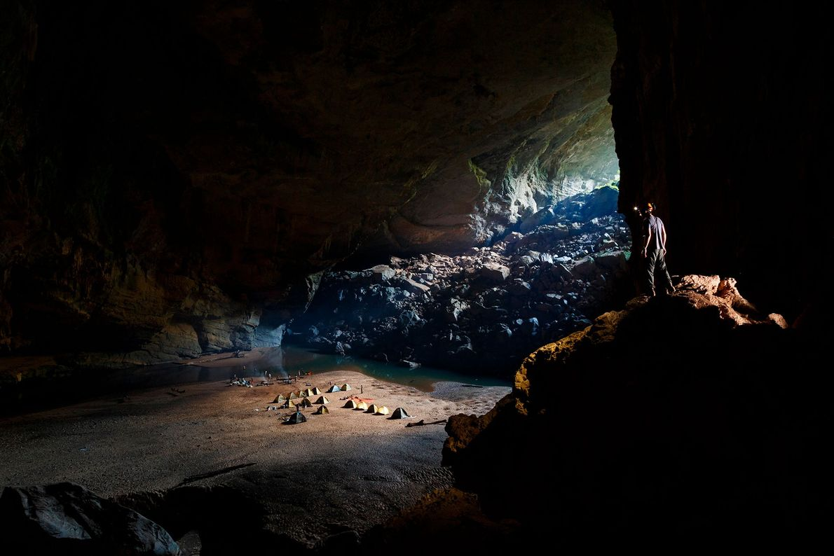 A caver looks over a group's camp for the night inside Hang Én, a cave in ...