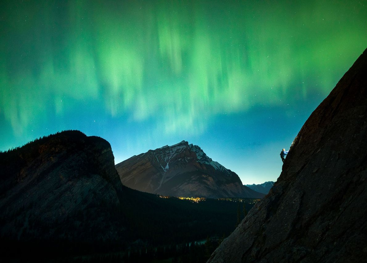 An aurora spreads across the sky above a climber on Rundlehorn in Banff National Park in ...