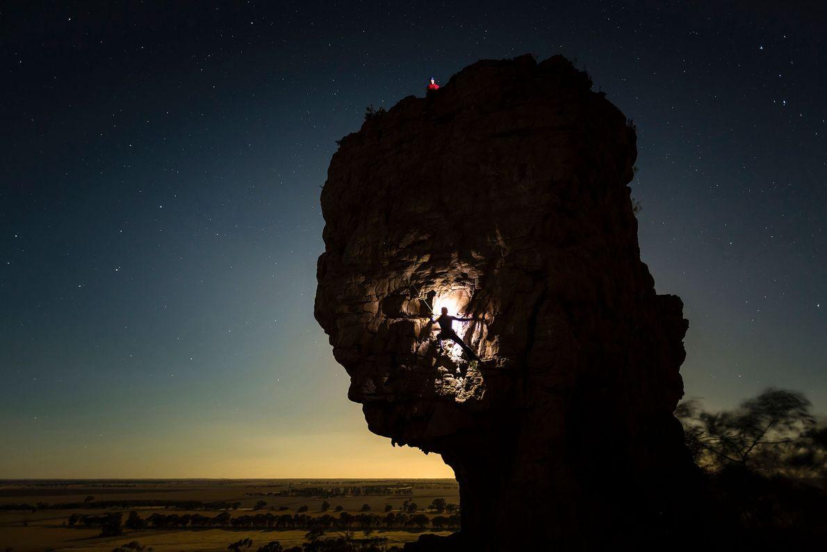 A climber illuminates Mount Arapiles with a headlamp as she climbs in Victoria, Australia.