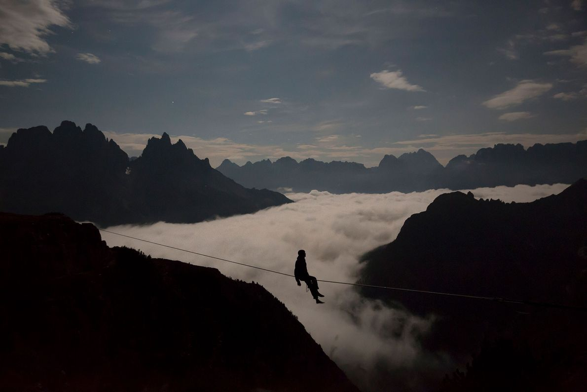 A highliner sits on a rope spread across peaks in the Italian Dolomites.