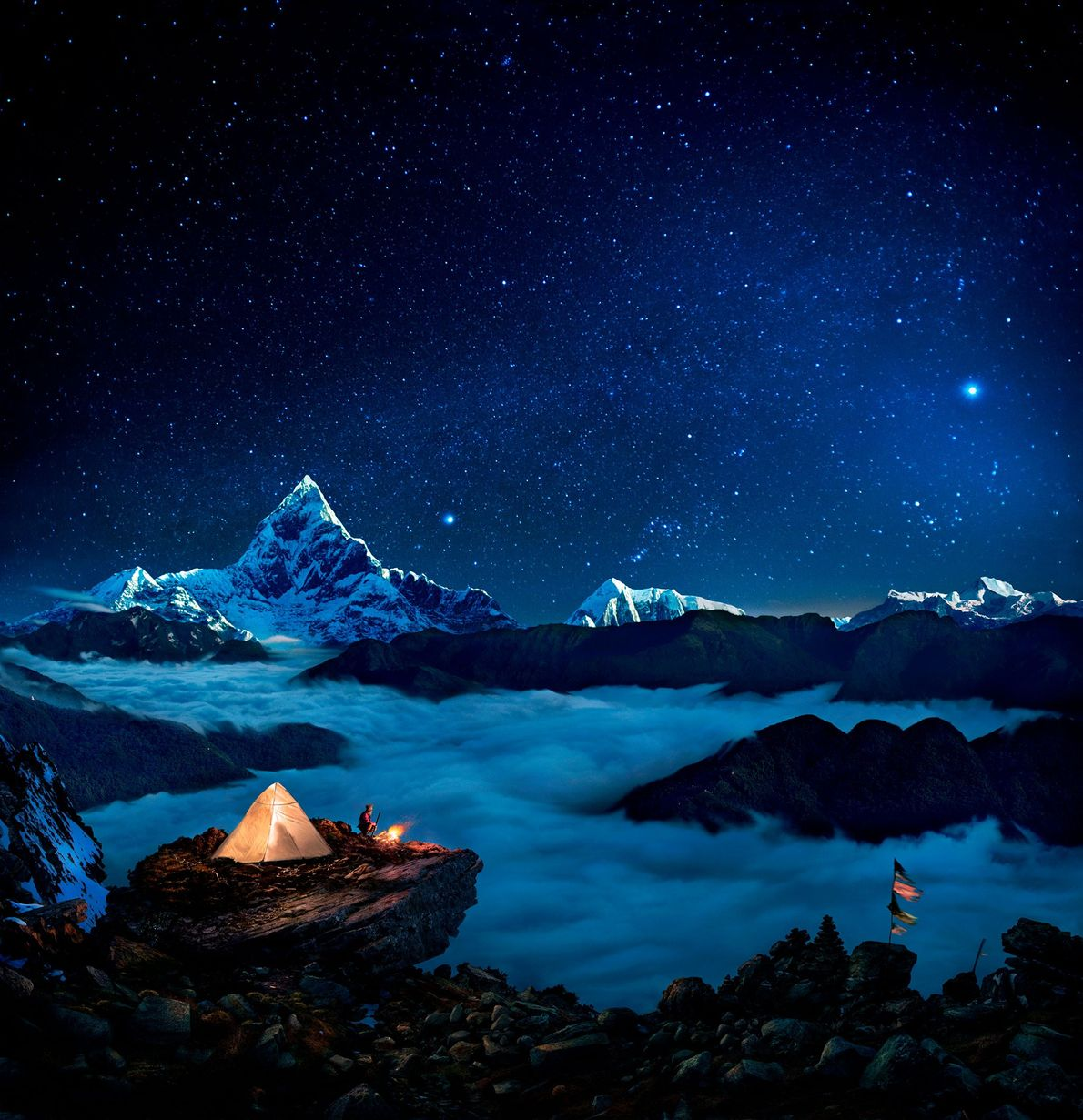 Stars shine down on campers at a bonfire in Kaski, Nepal.