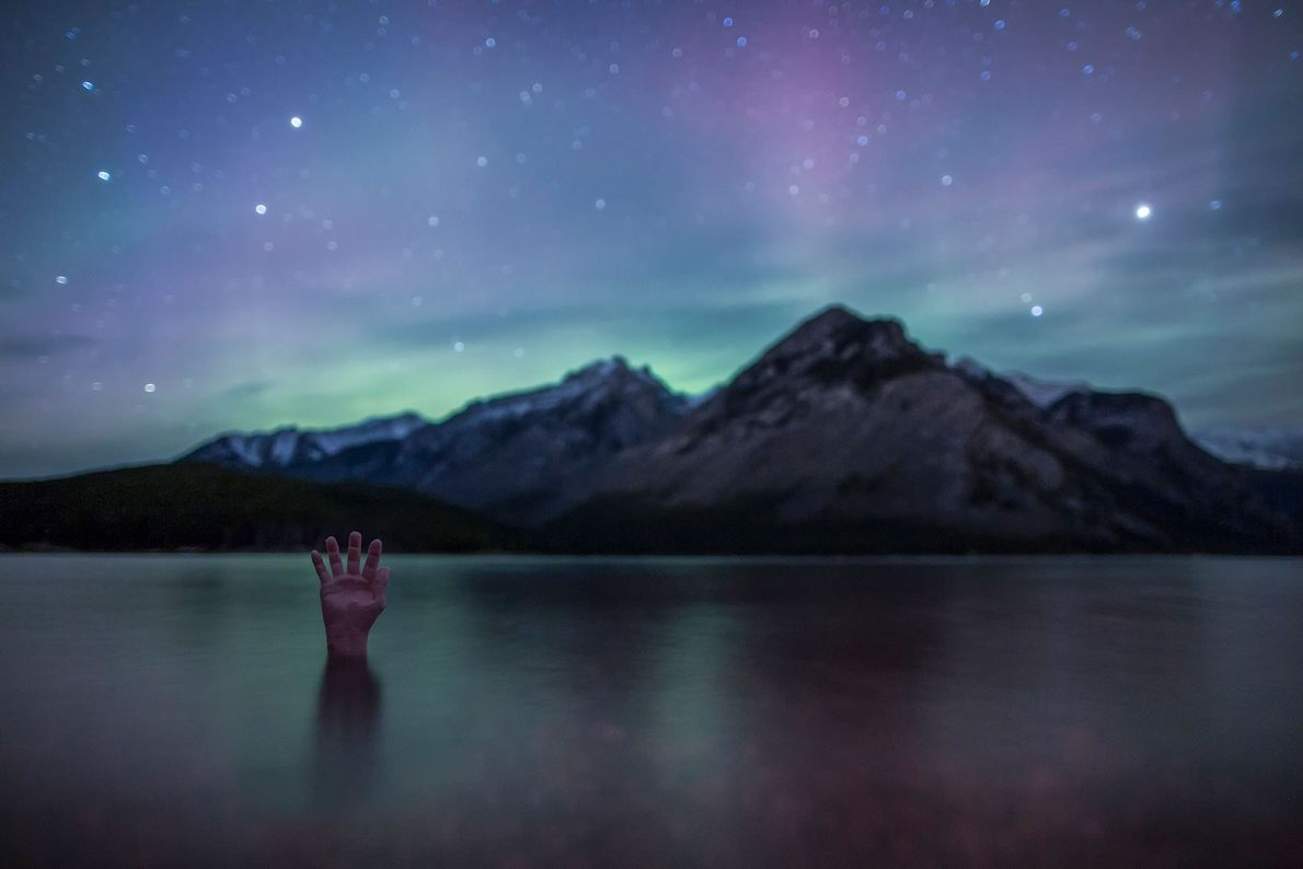 A hand reaches up from the under the surface of Lake Minnewanka in Canada's Banff National ...