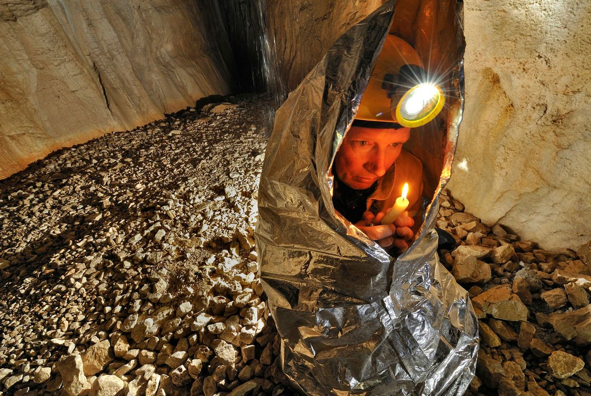 A caver uses a candle and an insulated blanket to attempt to stay warm in Gouffre ...
