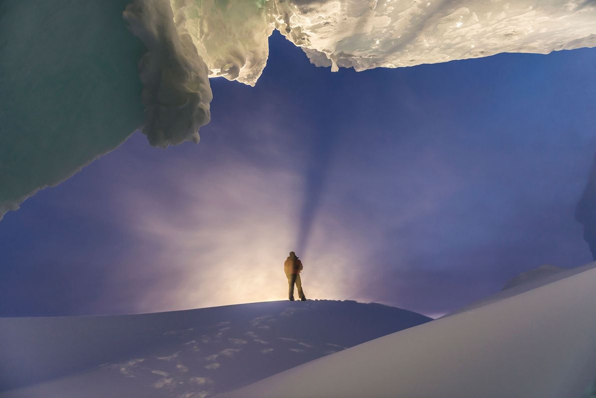 A man stands at the entrance of an ice cave during a winter visit to Antarctica.