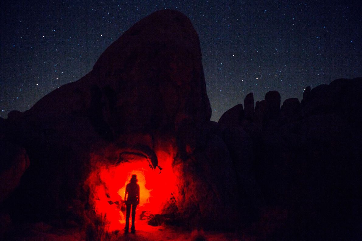 A hiker shines a headlamp on a rock formation in California's Joshua Tree National Park, USA.