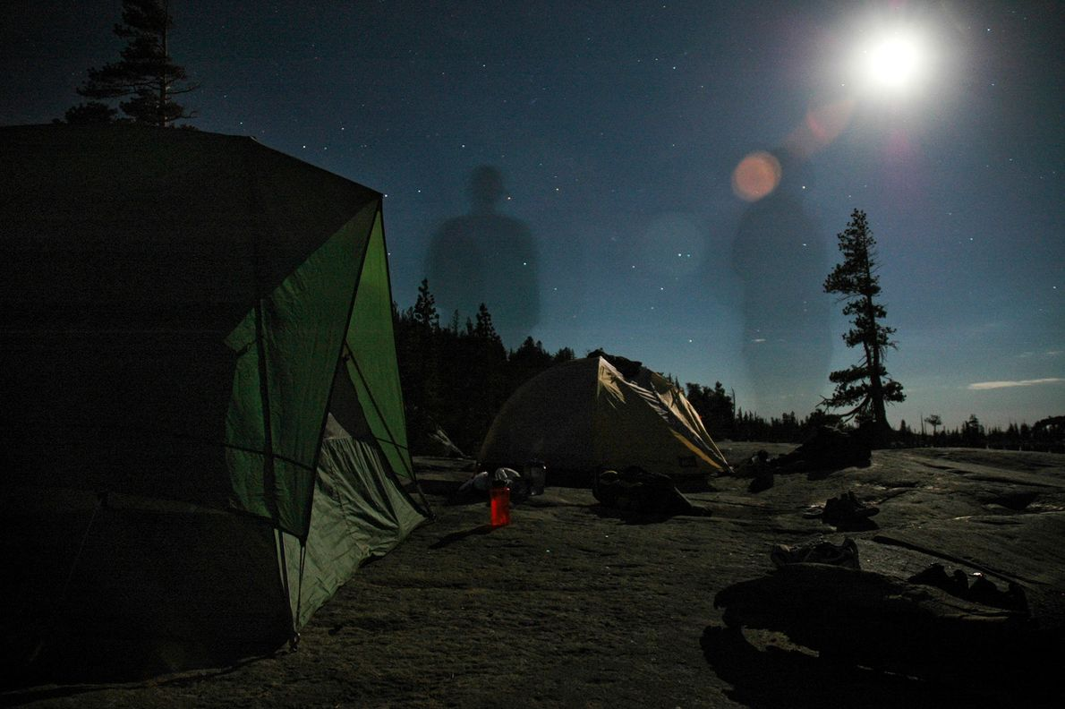 The shadow of a man on an evening stroll stands tall against the night sky in ...