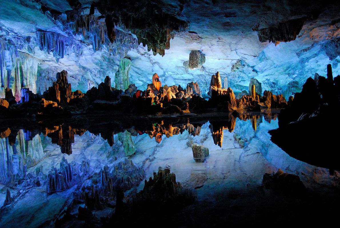 Shining waters inside Reed Flute Cave in Guilin, China, reflect images of the cave's eerie rock ...