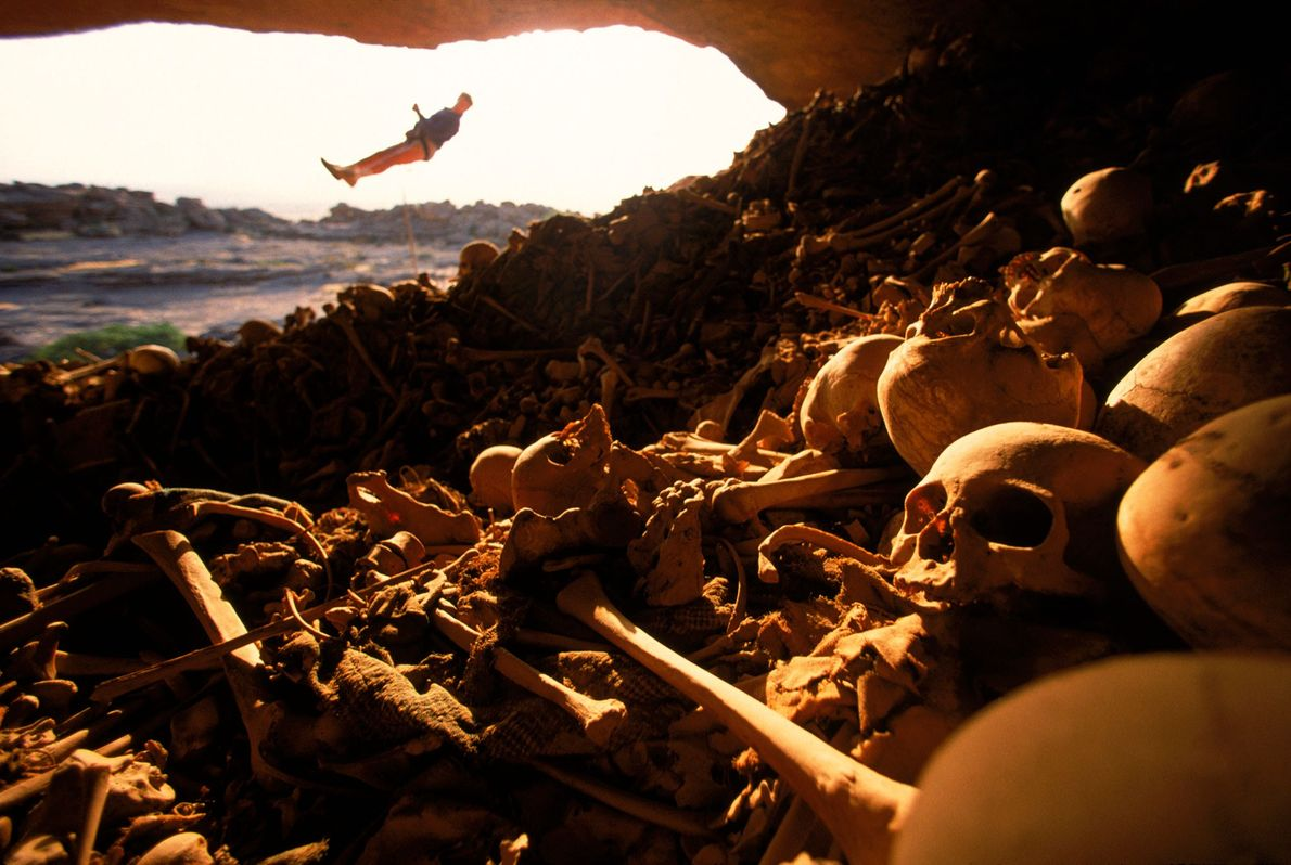 A rock climber hangs at the entry of a bone-filled burial cave in the cliffs of ...