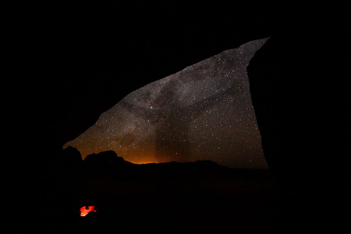 A shadow of a person darkens the starry sky in Namibia.
