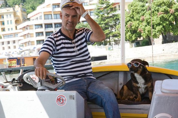 The helmsman of the glass-boat water taxi with his dog in the Kvarner Riviera