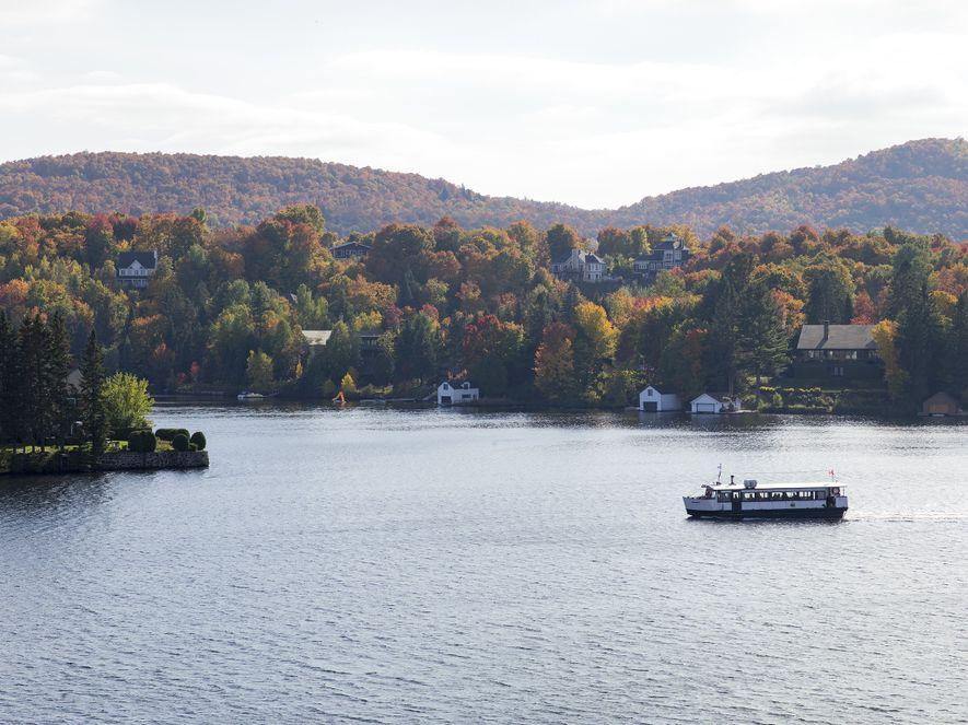 A boat floats on Lac des Sables past the shores of Sainte-Agathe-des-Monts, a small town set ...