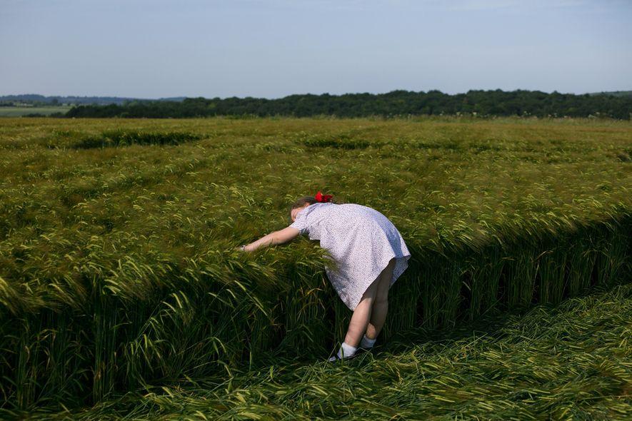 A young girl explores a crop circle near Sixpenny Handley in Dorset, England.