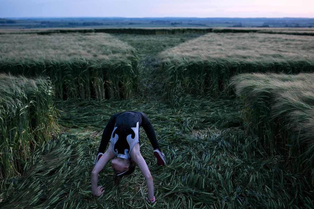 A child plays in a crop circle during dusk near Sixpenny Handley in Dorset.