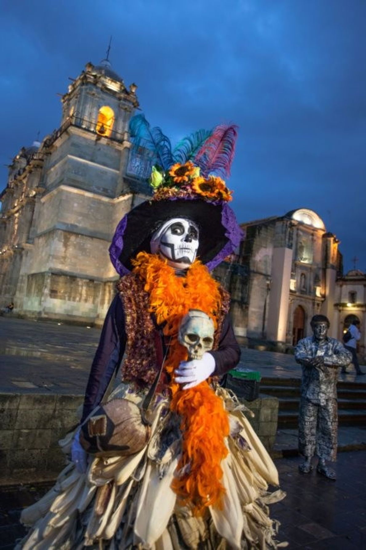 A lady dressed as La Calaveras Catrin and wearing a corn husk skirt outside the cathedral ...