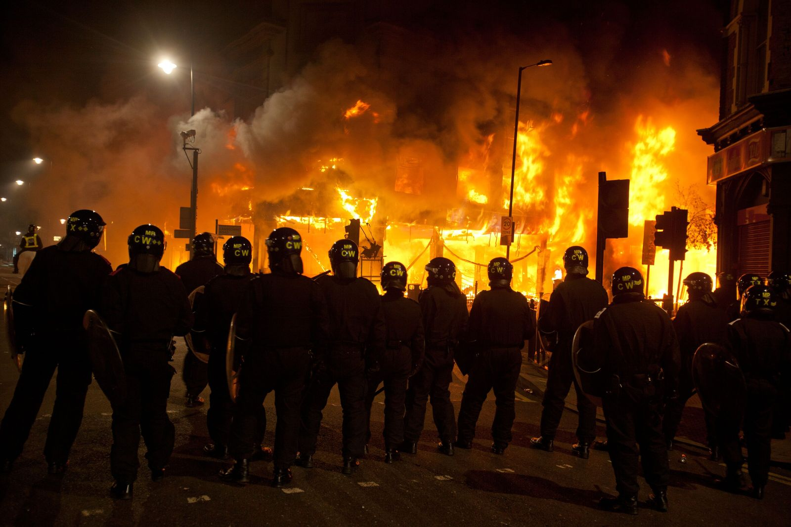 Police stand amidst rioting in Tottenham, London, in 2011. Civil unrest was spurred by the death ...