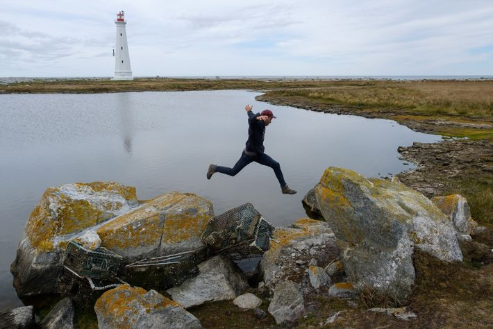 Darren Hudson, lumberjack and owner of Barrington's Wild Axe company, jumps over washed-up lobster traps in ...