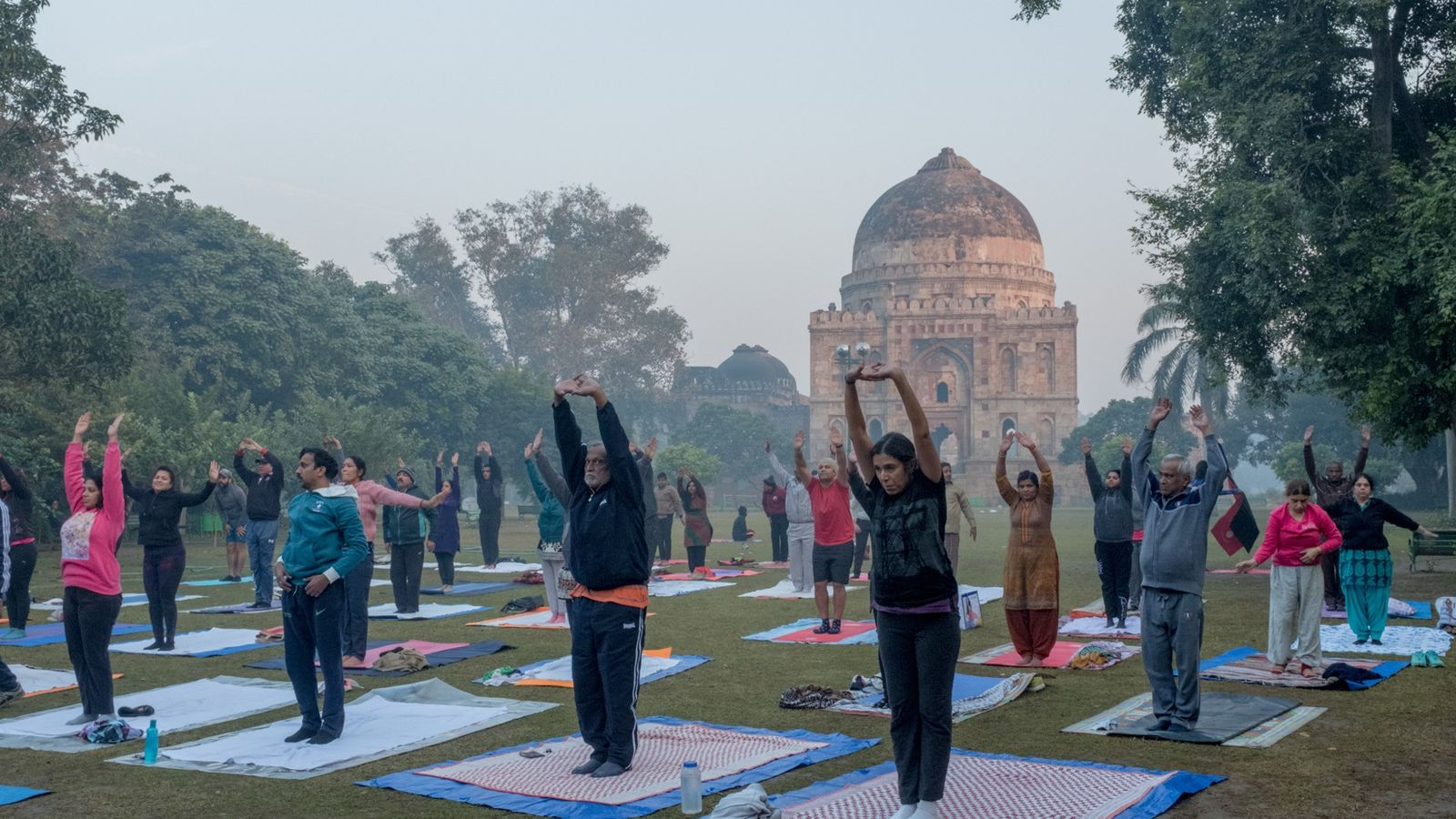People practice yoga in the Lodi Gardens in front of the Bada Gumbad. Air pollution levels ...