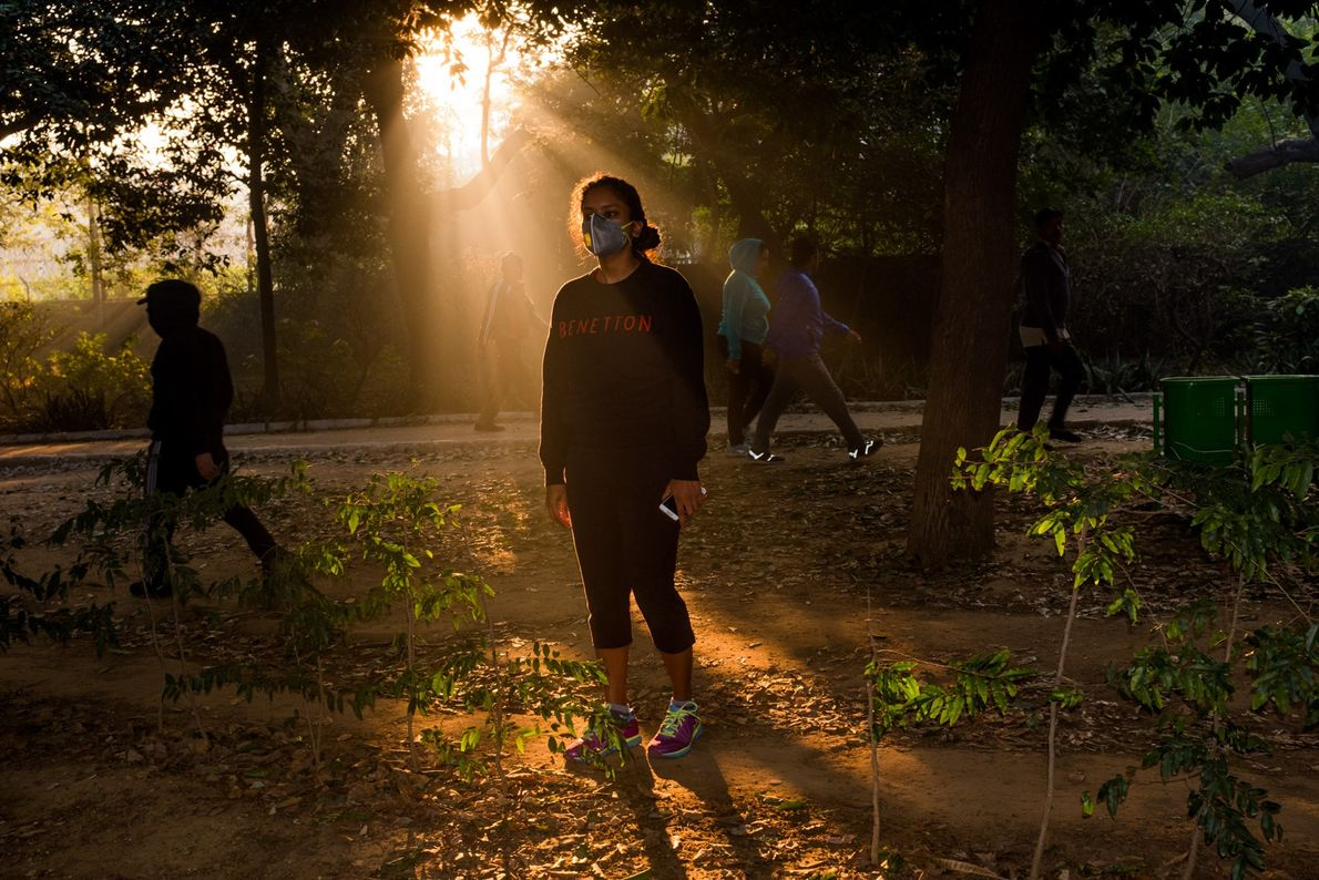 A young woman wears a mask during a morning walk in the Lodi Gardens.