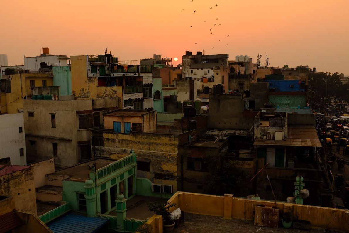 The sun sets over the rooftops of Old Delhi.