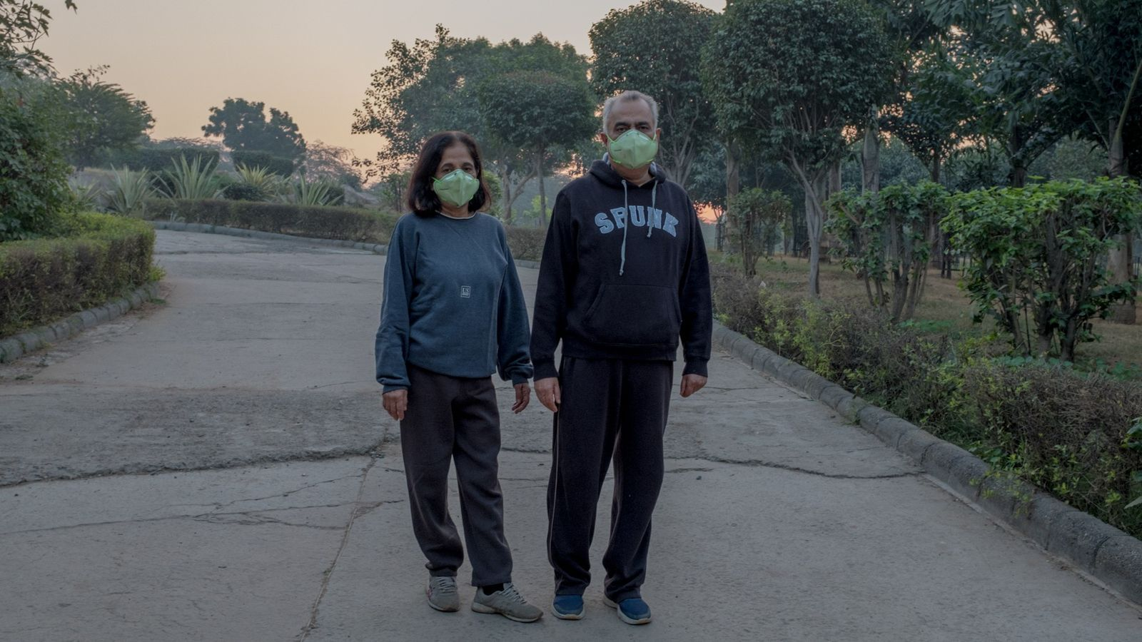 A couple wears masks while on their morning walk in Astha Kunj Park near the Lotus ...