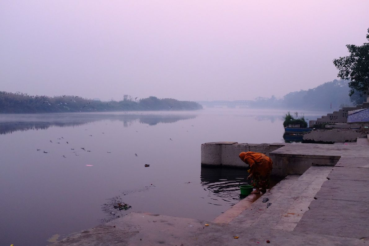 A woman gathers water in the early morning along the Yamuna river.
