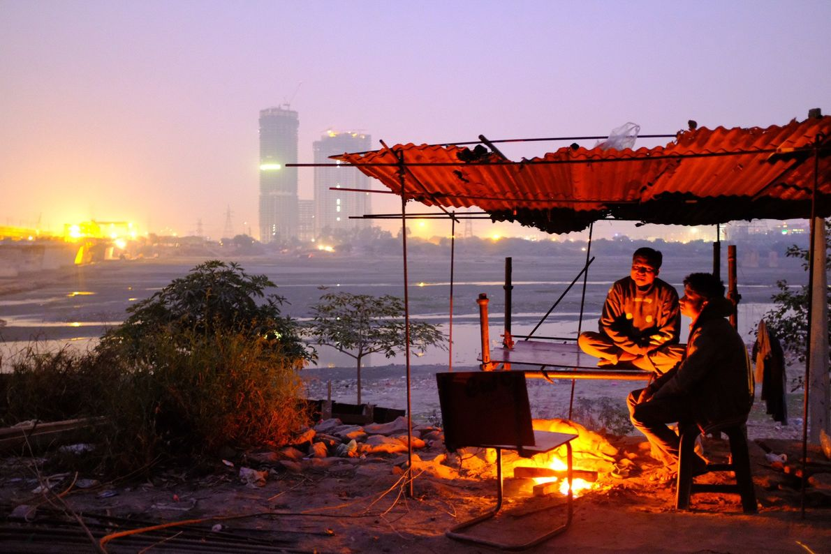 Construction workers gather around a bonfire at end of day near Okhla Barrage. Construction and burning ...