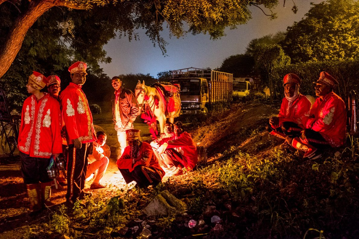 Musicians warm themselves by a fire. Construction activities, vehicular pollution, road dust, waste burning, and localized ...
