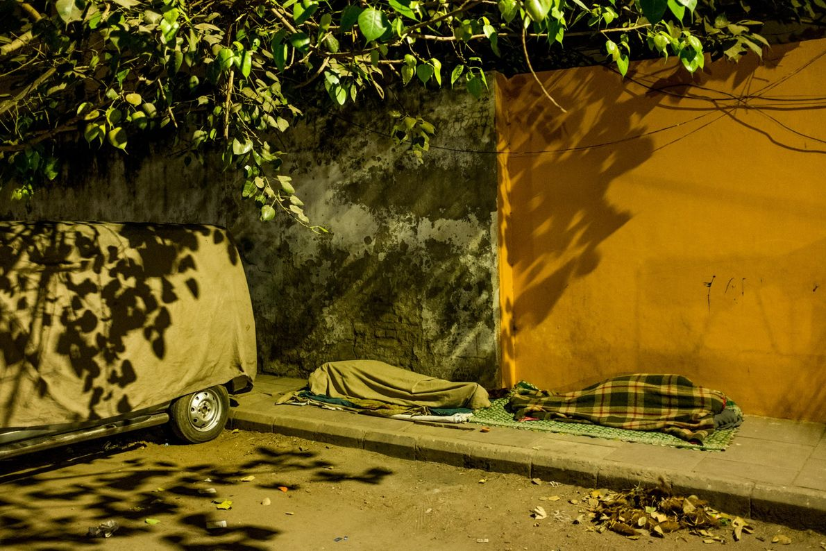 People sleeping outside along Padam Chand Marg in Old Delhi.