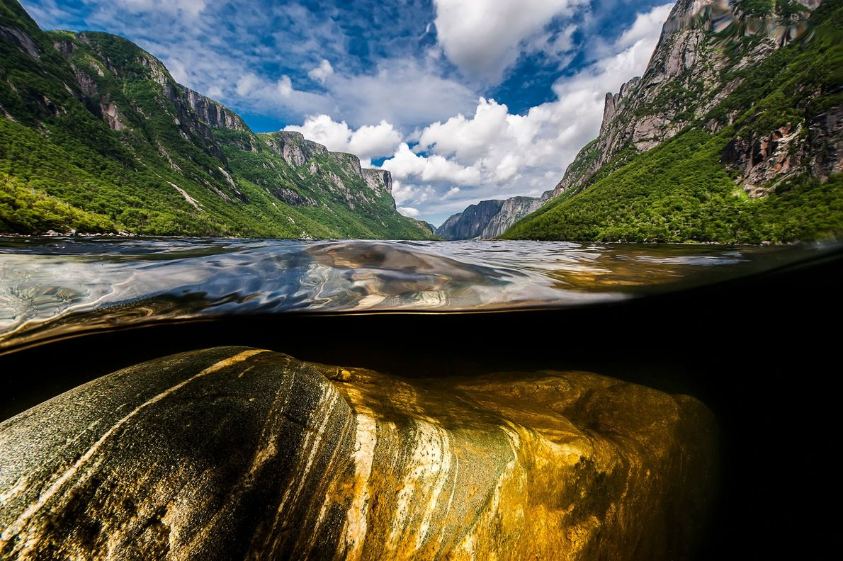 Steep rock walls soar 2,000 feet above Western Brook Pond, a fjord in Gros Morne National ...